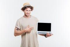举行黑屏膝上型计算机和指向的微笑的可爱的年轻人 库存照片