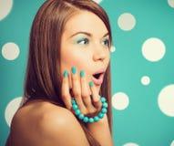 举行绿松石镯子机智的年轻美丽的惊奇的妇女 免版税库存图片