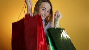 举行购物袋和微笑的美丽的女孩 股票视频