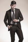 举行他的性感的年轻商人领带 免版税库存照片