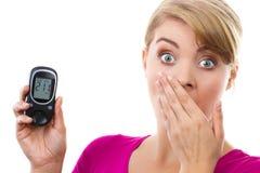 举行glucometer,测量和检查糖水平,糖尿病的概念的震惊妇女 库存照片