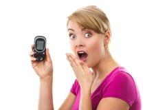 举行glucometer,测量的糖水平,糖尿病的概念的震惊妇女 库存照片