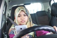 举行handphone的回教妇女,当驾驶时 免版税图库摄影