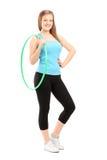 举行hula-hoo的一个年轻女运动员的全长potrait 免版税图库摄影