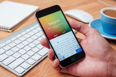举行Iphone和使用Instagram应用的手 免版税库存图片