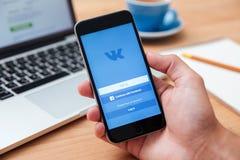 举行iphone 6显示的Vkontakte app的人 库存照片