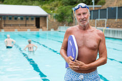 举行kickboard的微笑的老人在游泳池边 免版税库存图片
