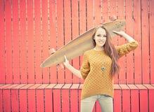 举行longboard的美丽的红发女孩站立在红色墙壁附近 免版税库存照片