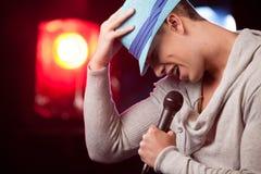 举行mic和唱歌的英俊的人 库存照片