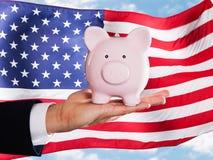 举行Piggybank的商人 库存照片