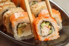举行Uramaki加利福尼亚和另外寿司r的两双筷子 库存照片