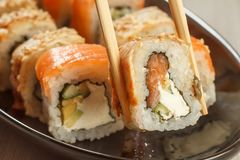 举行Uramaki用欧洲康吉鳗和另外寿司的两双筷子 免版税图库摄影