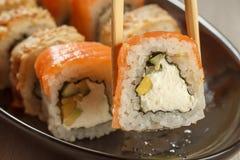 举行Uramaki费城和另外寿司的两双筷子 库存图片