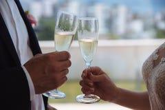 举行wineglases用香槟的两只手 免版税库存照片