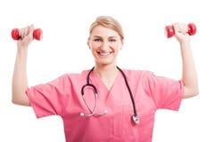举训练重量的营养师妇女 免版税库存图片