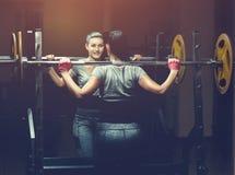 举重的杠铃的亭亭玉立的女孩爱好健美者站立在镜子前面,当训练在健身房时 库存图片