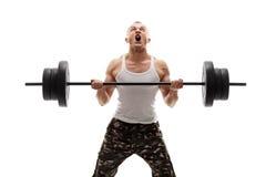 举重的杠铃的坚定的年轻爱好健美者 免版税库存图片