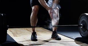 举重运动员拍的手特写镜头在杠铃锻炼前的在 免版税库存图片