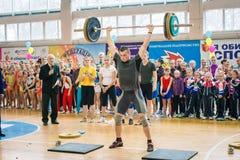 举重运动员表示表现冠军的在啦啦队欢呼,年轻人举重的杠铃,杠铃重量- 100 免版税库存图片