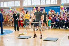 举重运动员表示表现冠军的在啦啦队欢呼,年轻人举重的杠铃,杠铃重量- 10 免版税库存照片