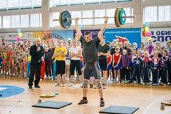 举重运动员表示表现冠军的在啦啦队欢呼,年轻人举重的杠铃,杠铃重量- 10 免版税图库摄影