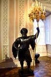 举金黄枝形吊灯蜡烛的卫兵雕象 免版税图库摄影