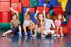 举他们的在学校健身房的孩子手  免版税库存照片