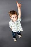 举他的手指的聪明的逗人喜爱的小孩为问题 免版税库存照片
