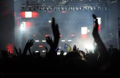 举他们的手的人群在音乐会 免版税库存图片