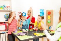 举他们的手的孩子在公路安全教训 免版税库存图片