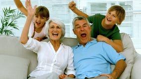 举他们的胳膊的祖父母和孩子在客厅 影视素材