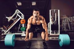 举Deadlift的肌肉人 库存图片