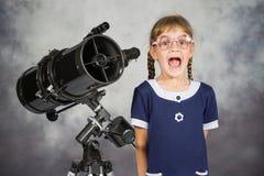 什么愉快地惊奇的女孩天文学家他在望远镜看见了 库存照片