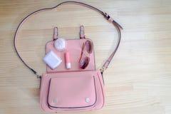 什么来自一个开放袋子?化妆用品、妇女银和辅助部件落在桃红色提包外面 库存图片