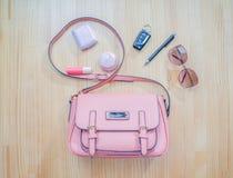 什么来自一个开放袋子?化妆用品、妇女银和辅助部件落在桃红色提包外面 免版税图库摄影