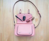 什么从一个开放袋子出来?妇女汽车钥匙、太阳镜和笔从一个桃红色提包出来 库存照片