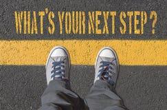 什么` s您的下一个步骤?与运动鞋的印刷品在柏油路 库存照片