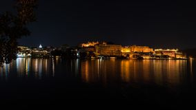 乌代浦都市风景在夜之前 在湖Pichola,旅行目的地的庄严城市宫殿反射的光在拉贾斯坦,印度 免版税库存照片
