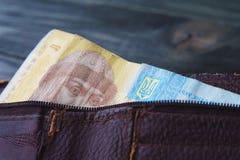 乌克兰人一hrivna票据在木的老破旧的皮革钱包里 免版税库存图片