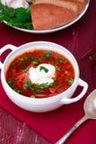 乌克兰传统罗宋汤 在白色碗的俄国素食红色汤在红色木背景 罗宋汤,博尔希用甜菜 图库摄影