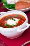 乌克兰传统罗宋汤 在白色碗的俄国素食红色汤在红色木背景 罗宋汤,博尔希用甜菜 免版税图库摄影