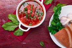 乌克兰传统罗宋汤 在白色碗的俄国素食红色汤在红色木背景 顶视图 罗宋汤,博尔希机智 免版税库存照片