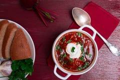 乌克兰传统罗宋汤 在白色碗的俄国素食红色汤在红色木背景 顶视图 罗宋汤,博尔希机智 免版税图库摄影