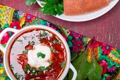 乌克兰传统罗宋汤 在白色碗的俄国素食红色汤在红色木背景 顶视图 罗宋汤,博尔希机智 免版税库存图片