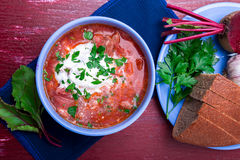 乌克兰传统罗宋汤 在蓝色碗的俄国素食红色汤在红色木背景 罗宋汤,博尔希用甜菜  库存图片