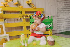 乌克兰全国服装的孩子有复活节蛋糕的 文本幸福 免版税库存照片