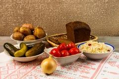乌克兰全国盘是被烘烤的土豆 在皮肤的被烘烤的整个土豆用德国泡菜、烂醉如泥的蕃茄和黄瓜 免版税库存图片