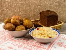 乌克兰全国盘是被烘烤的土豆 在皮肤的被烘烤的整个土豆用德国泡菜、烂醉如泥的蕃茄和黄瓜 免版税图库摄影