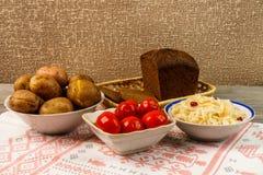 乌克兰全国盘是被烘烤的土豆 在皮肤的被烘烤的整个土豆用德国泡菜、烂醉如泥的蕃茄和黑黑麦面包 图库摄影
