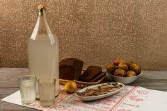 乌克兰全国饮料和快餐 月光大瓶和玻璃在老木桌上的 免版税图库摄影